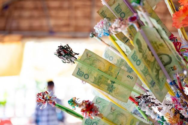 Thaise boeddhisten verdienen een verdienste met bankbiljet in songkran-festival. songkran festival is de traditionele nieuwjaarsviering in thailand. Premium Foto