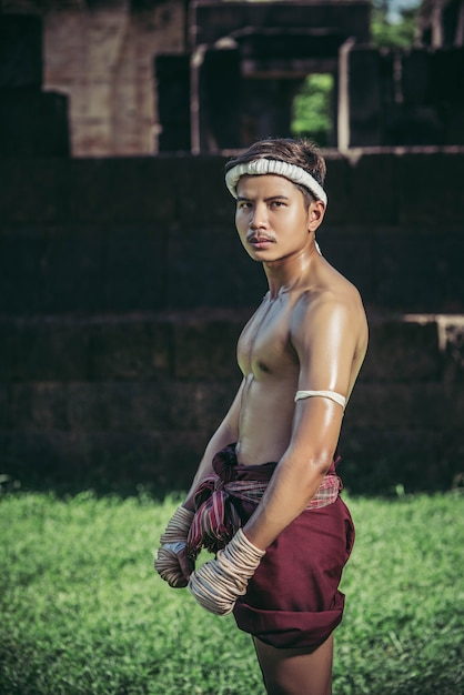 Thaise boksers wikkelen de tape in de handen en gaan op het gazon staan. Gratis Foto
