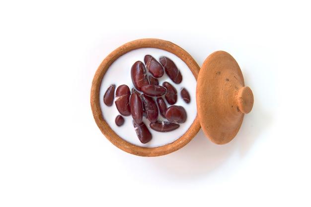 Thaise die dessert rode boon in kokosmelk met kleipot op witte achtergrond wordt geïsoleerd Premium Foto