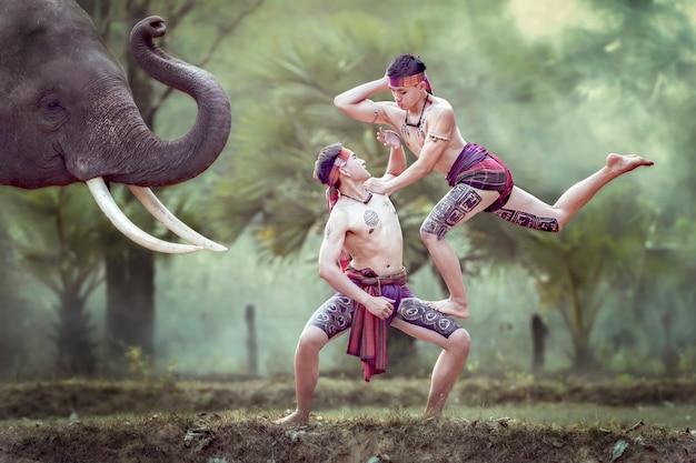 Thaise jongens oefenen oude boksdansen voor de olifanten, een van de kunst van het thaise volk. Premium Foto