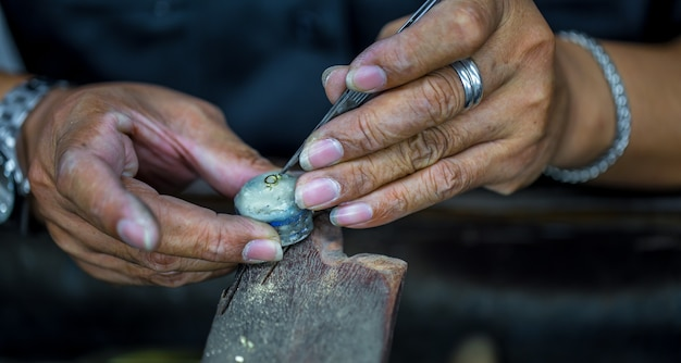 Thaise juwelier, behandelt de sieraden en edelstenen in de werkplaats, het proces van het maken van sieraden, close-up Gratis Foto