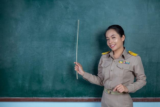 Thaise leraar in officiële outfit lesgeven voor bord Gratis Foto