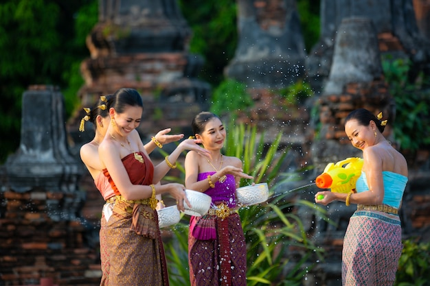 Thaise meisjes in thais traditioneel kledings bespattend water tijdens festival songkran festival, ayutthaya, thailand. Premium Foto