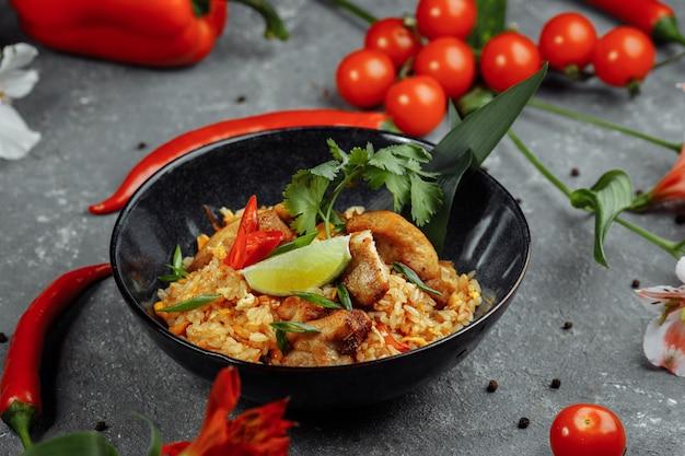Thaise rijst met kip. thais gerecht van rijst, kip, jalta ui, mais, ananas, tomaat, sojasaus, chilipasta, koriander, limoen, chilipeper groene ui kruiden Premium Foto