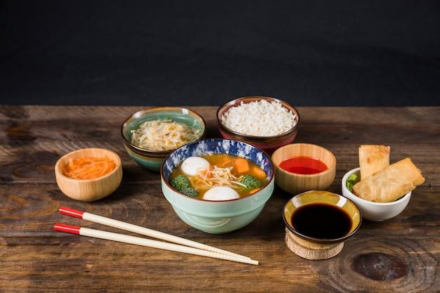 Thaise soep; rijst; saus; bonen spruiten; salade en gefrituurde loempia's op tafel tegen zwarte muur Gratis Foto