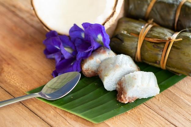 Thaise traditionele dessert kleverige rijst met bananen (khao tom mat) op houten achtergrond Premium Foto