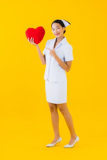 Thaise verpleegster van de portret de mooie jonge aziatische vrouw met de vorm van het harthoofdkussen Gratis Foto