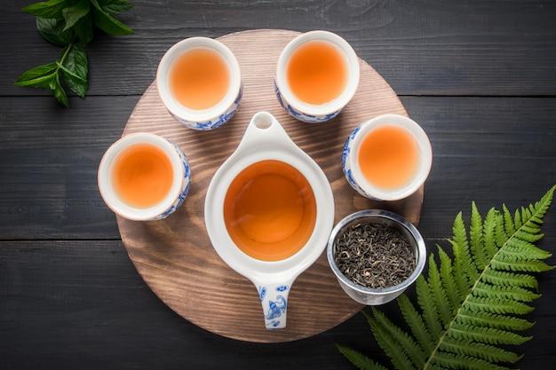 Thee ceremonie. kopjes groene thee met munt en waterkoker op donker. chinees thee concept. uitzicht van boven. Premium Foto