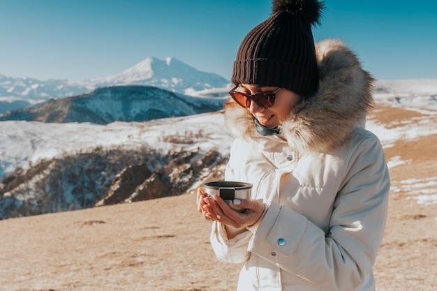 Thee drinken in de bergen. reiziger met een mok warme drank in de bergen. Premium Foto