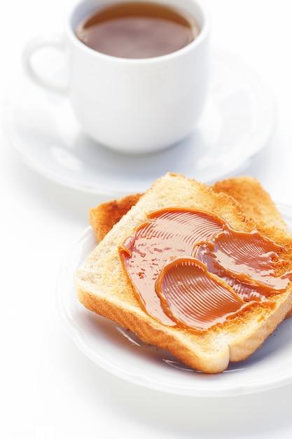 Thee en toost met karamel op wit wordt geïsoleerd dat Premium Foto