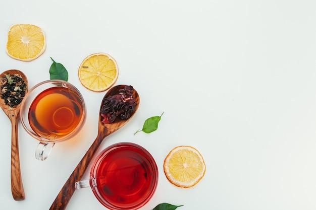 Thee in een glazen beker met specerijen en kruiden. bovenaanzicht witte achtergrond Premium Foto