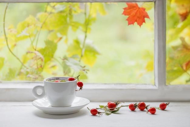 Thee met bessen van een dogrose op een vensterbank Premium Foto