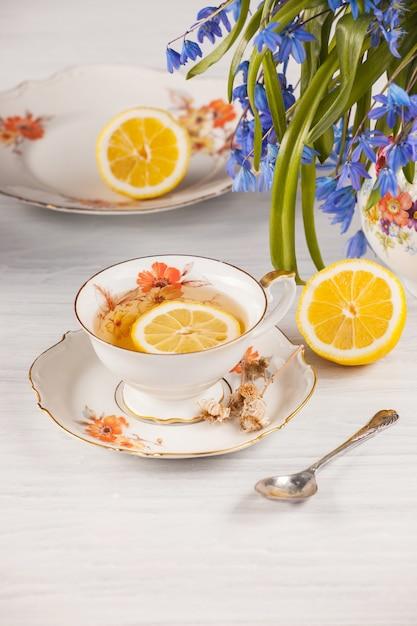 Thee met citroen en boeket van blauwe sleutelbloemen op de tafel Gratis Foto