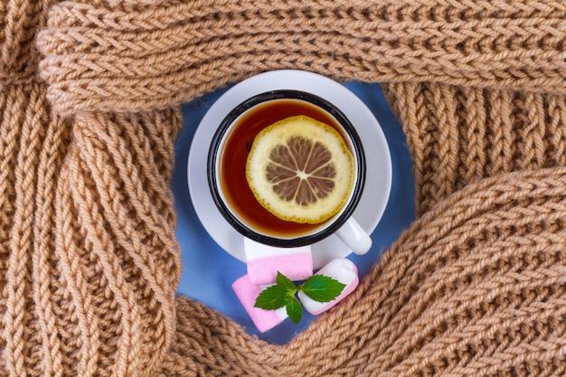 Thee met citroen, gebreide sjaal, een stuk verse munt en marshmallows Premium Foto