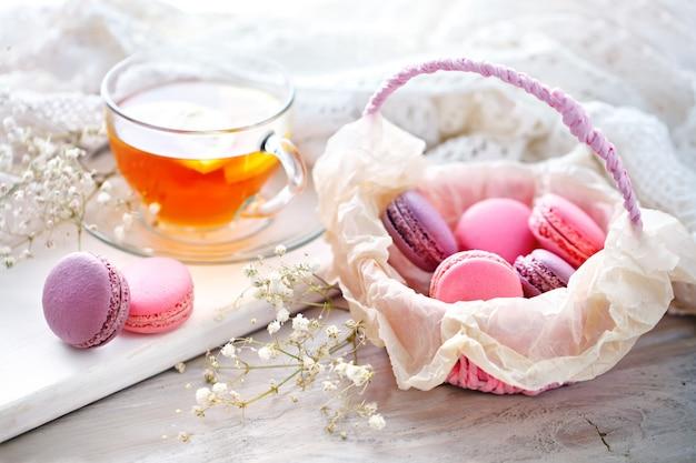 Thee met citroen, wilde bloemen en macaron op witte houten tafel. Premium Foto