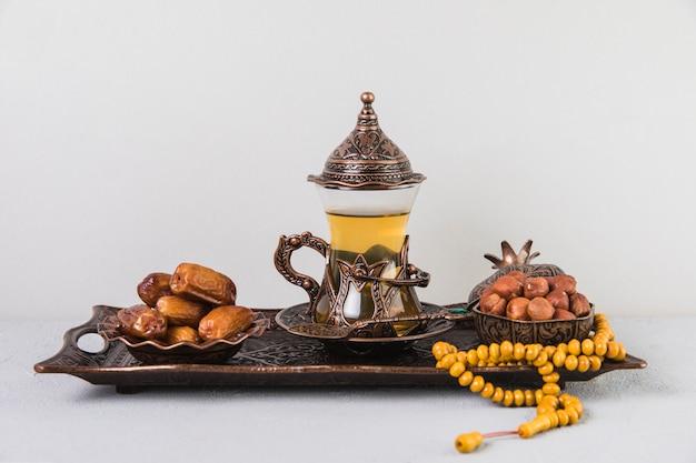 Theeglas met dadelsfruit en parels op dienblad Gratis Foto