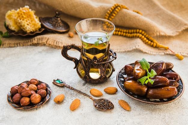 Theeglas met dadelsfruit en verschillende noten Gratis Foto