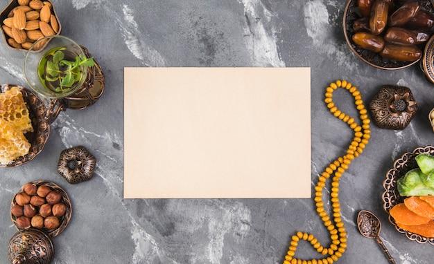 Theeglas met dadelsfruit, kralen en blanco papier Gratis Foto