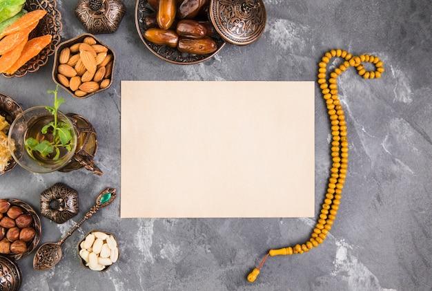 Theeglas met dadelsfruit, kralen en papier Gratis Foto
