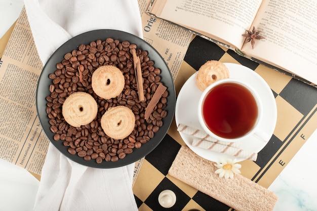 Theekop en koekjesschotel op een schaakbord Gratis Foto