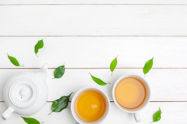 Theepot en kop theeën op een witte houten achtergrond Premium Foto