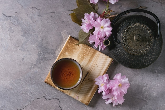 Theepot en kopje thee met bloesem tak Premium Foto