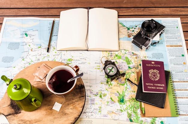 Theepot, kompas, paspoort, fotocamera en blok aantekeningen op de kaart Premium Foto