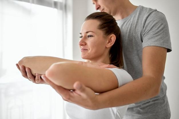 Therapeut die fysiotherapie ondergaat met een vrouwelijke patiënt Gratis Foto
