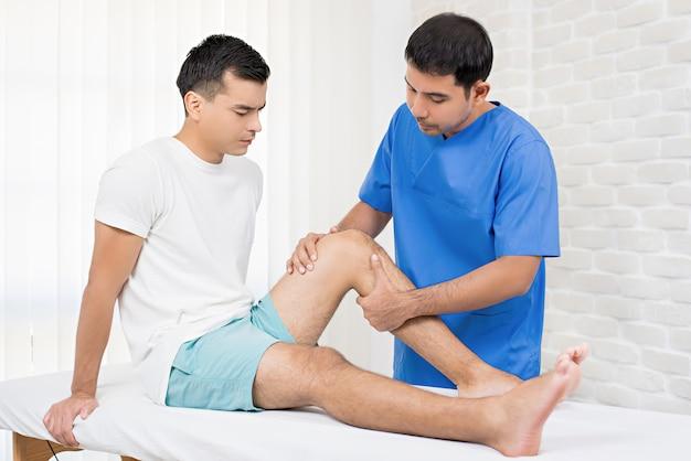 Therapeut die gewonde knie van mannelijke patiënt in het ziekenhuis behandelt Premium Foto