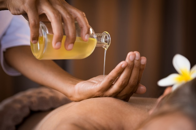 Therapeut gieten massageolie in spa Premium Foto