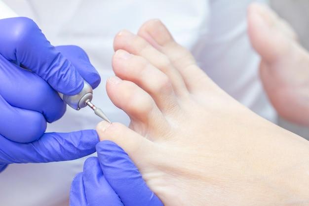 Therapeutische pedicure. meesterpodoloog doet hardware-pedicure. bezoek aan de podologie. voetbehandeling in de spa. kliniek van podiatria. Premium Foto