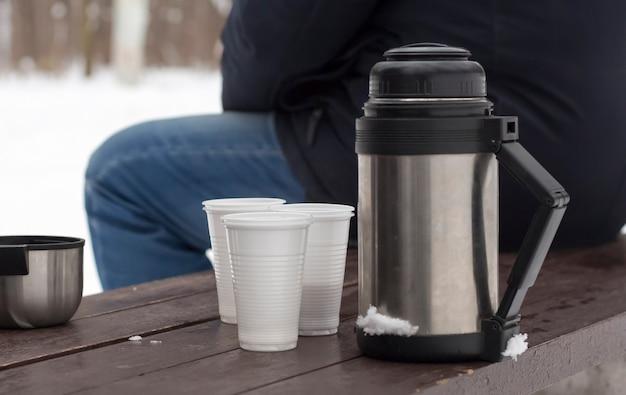 Thermoskan met kopjes op een bankje in de winter na een theekransje in de natuur. Premium Foto