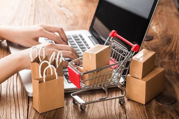Thuis online winkelen. kartons in een winkelwagentje op een laptop toetsenbord Premium Foto