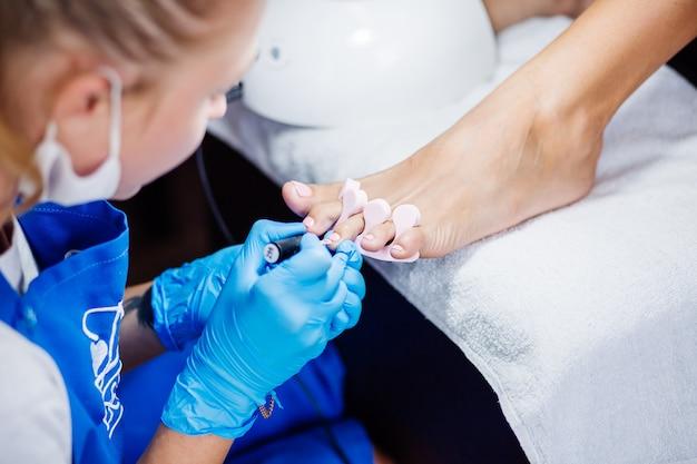 Thuis salon pedicure voetverzorging en nagel het proces van professionele pedicure master in blauwe handschoenen brengt lichtroze gellak aan Gratis Foto