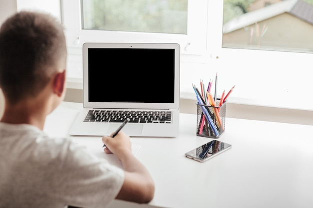 Thuis school door middel van online homeschooling. het kind zit achter de computer Premium Foto