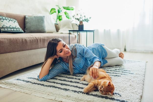 Thuis spelen met kat. jonge vrouw die op tapijt ligt en huisdier plaagt. Premium Foto