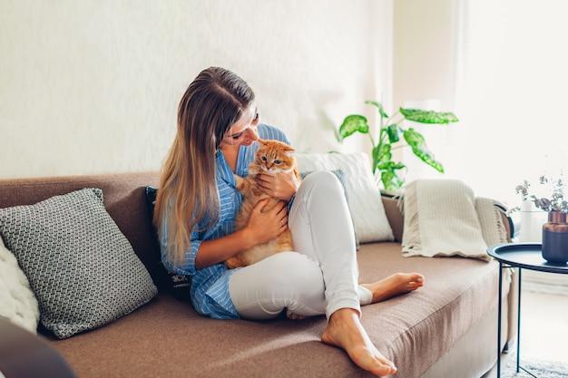 Thuis spelen met kat. jonge vrouw zittend op de bank met huisdier. Premium Foto