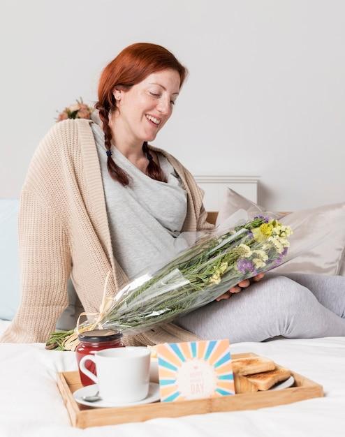 Thuis verrast de smiley zwangere vrouw Gratis Foto