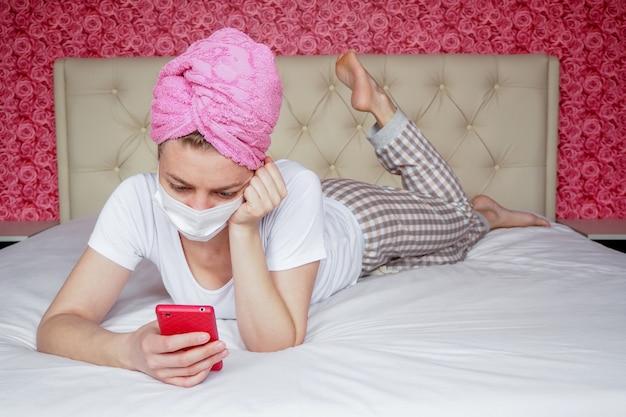 Thuisquarantaine. een jonge blanke blogger meisje in een beschermend medisch masker en een handdoek op haar hoofd ligt op het bed met een telefoon. recreatie en hobby's. communicatie op afstand in boodschappers. Premium Foto