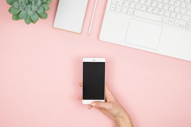 Thuiswerkruimte voor vrouwen. girl blogger werkt met telefoon en laptop. freelance concept. telewerker sms'en met laptop en internet, online werken. Premium Foto