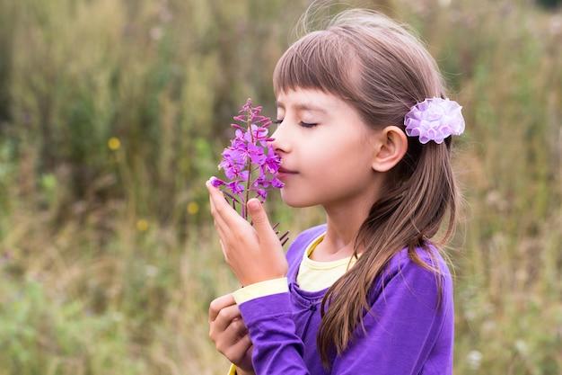 Tien-jaar-oude meisjes ruikende bloem Premium Foto