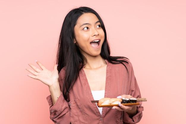 Tiener aziatisch meisje die sushi op roze muur met verrassingsgelaatsuitdrukking eten Premium Foto