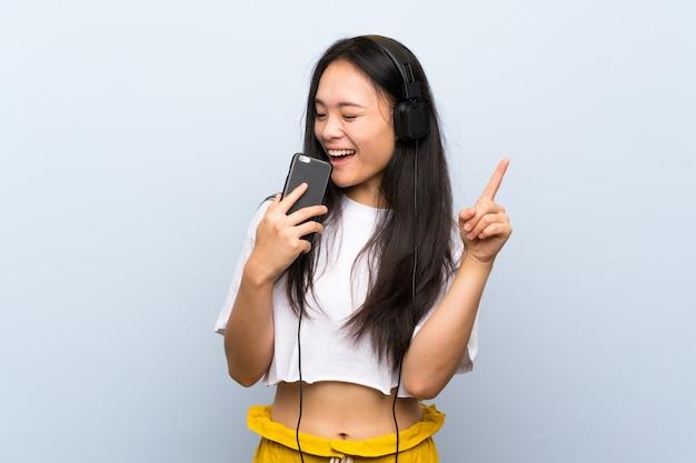 Tiener aziatische meisje het luisteren muziek over het geïsoleerde blauwe muur zingen Premium Foto