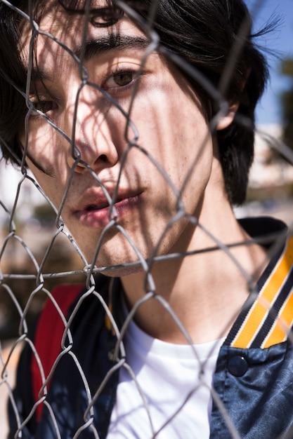Tiener die door omheining in straat kijkt Gratis Foto