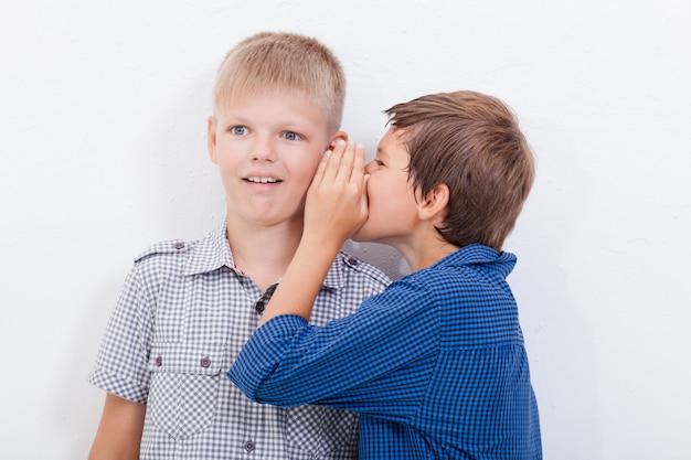 Tiener die in het oor een geheim fluistert aan friendl op witte achtergrond Gratis Foto