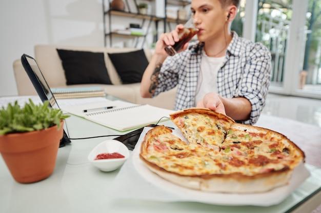 Tiener frisdrank drinken en pizza eten bij het voorbereiden van examens thuis Premium Foto