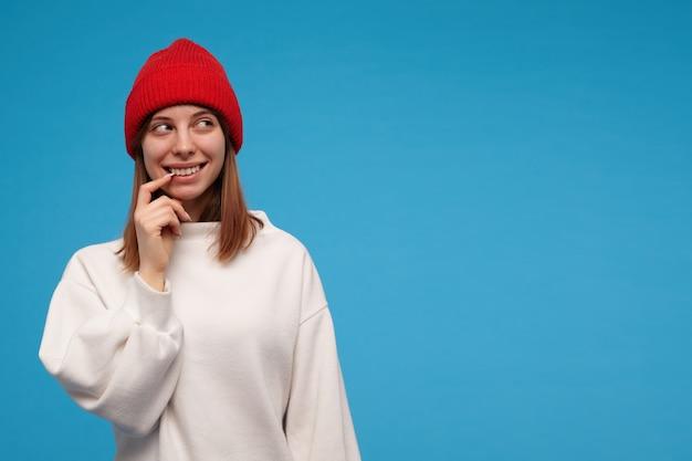 Tiener, gelukkig uitziende vrouw met donkerbruin haar. het dragen van een witte trui en een rode hoed. haar mondhoek aanraken en glimlachen. kijken naar rechts op kopie ruimte, geïsoleerd over blauwe muur Gratis Foto