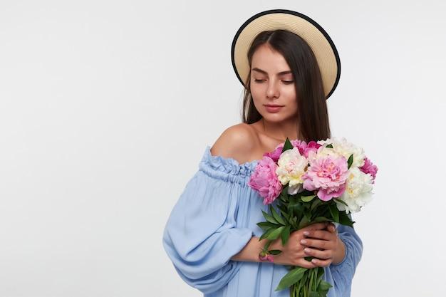 Tiener, gelukkig uitziende vrouw met donkerbruin lang haar. het dragen van een hoed en een blauwe jurk. met een boeket prachtige bloemen. kijkend naar de linker benedenhoek op kopie ruimte over witte muur Gratis Foto