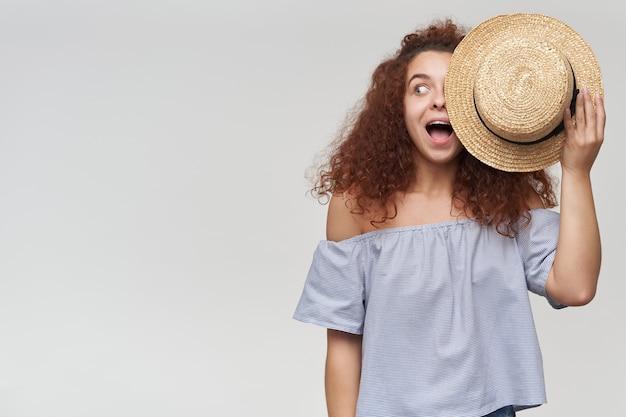 Tiener, gelukkig uitziende vrouw met gember krullend haar. een gestreepte blouse met blote schouders dragen en de helft van haar gezicht bedekken met een hoed. kijken naar links op kopie ruimte, geïsoleerd over witte muur Gratis Foto