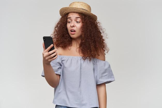 Tiener, gelukkig uitziende vrouw met gember krullend haar. gestreepte blouse en hoed met blote schouders. vasthouden en kijken naar haar smartphone, ongelukkig gezicht. tribune geïsoleerd over witte muur Gratis Foto